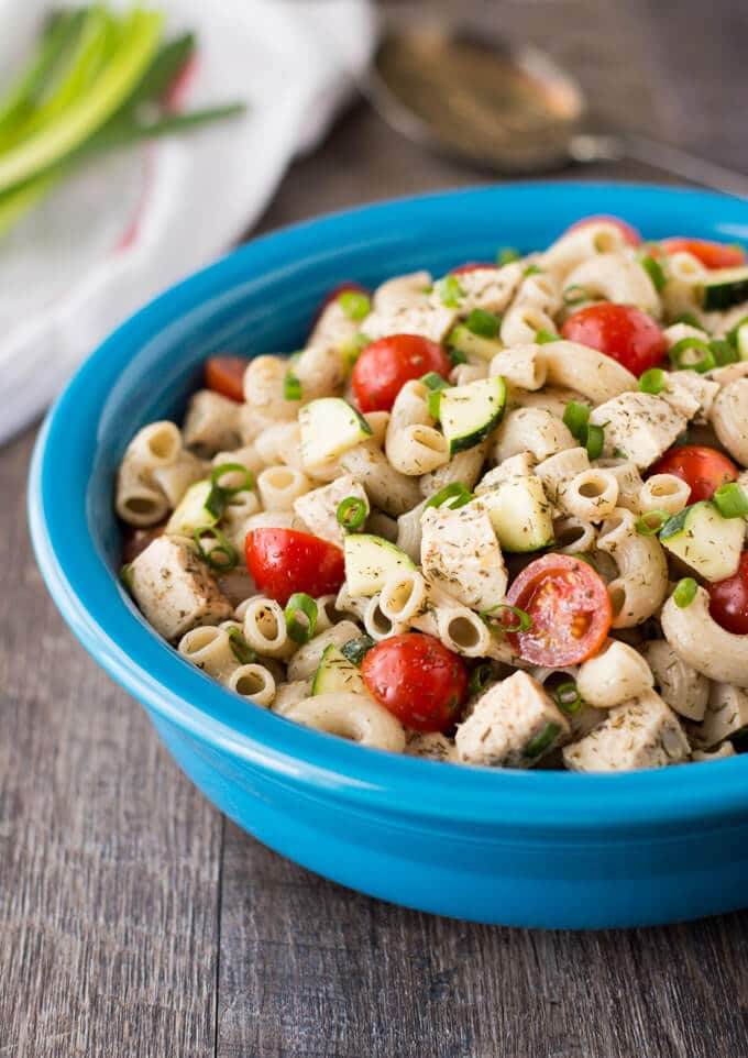 A blue bowl filled with macaroni, chicken, zucchini, and cherry tomatoes.