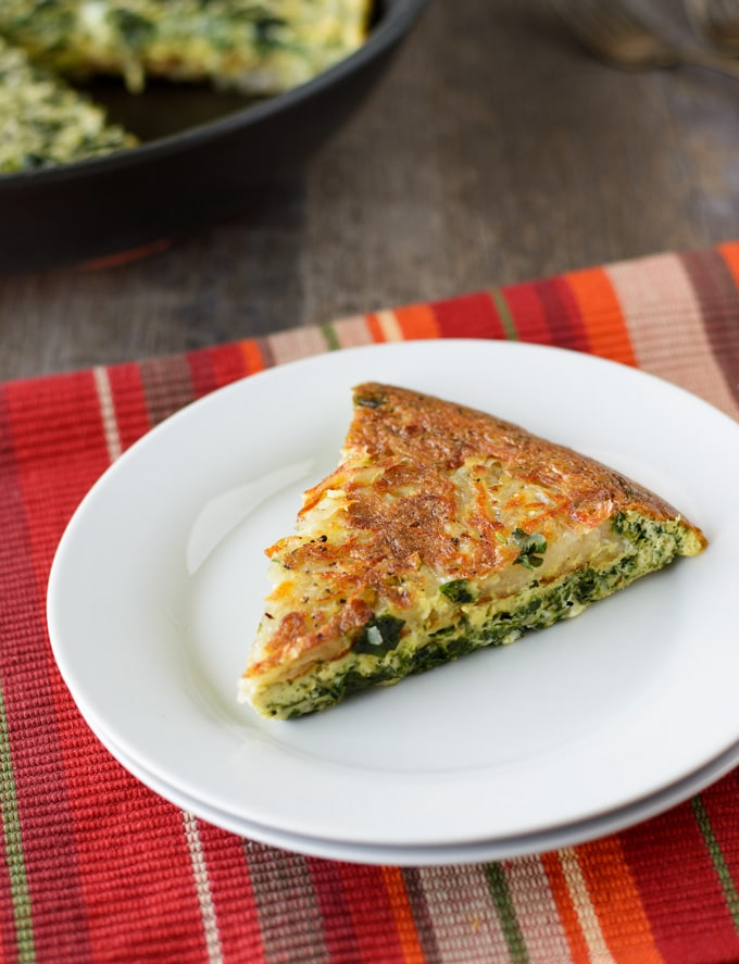 A slice of Hash Brown Frittata sitting on a small white plate.