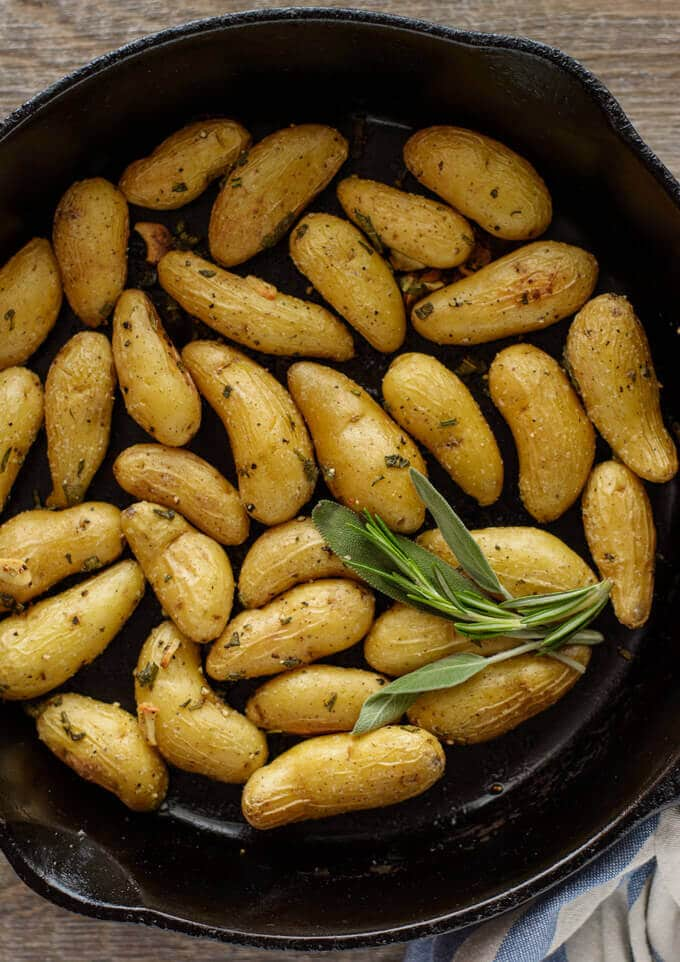 A cast iron skillet filled with roasted fingerling potatoes.
