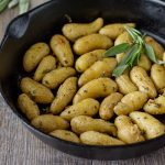 Roasted Fingerling Potatoes in a cast iron skillet with fresh herbs.