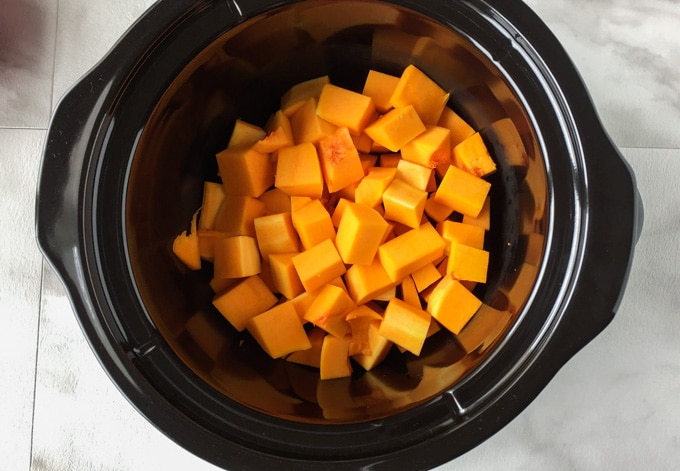 Chunks of butternut squash soup inside of a black crockpot.