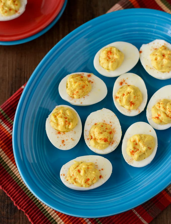 A blue platter with the Deviled Eggs topped with Paprika.