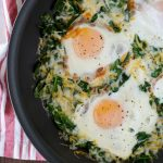 A non-stick skillet with wilted spinach, cheese and cooked eggs.