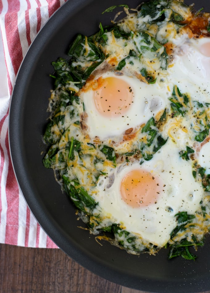 A skillet with wilted spinach, eggs and melted cheese.