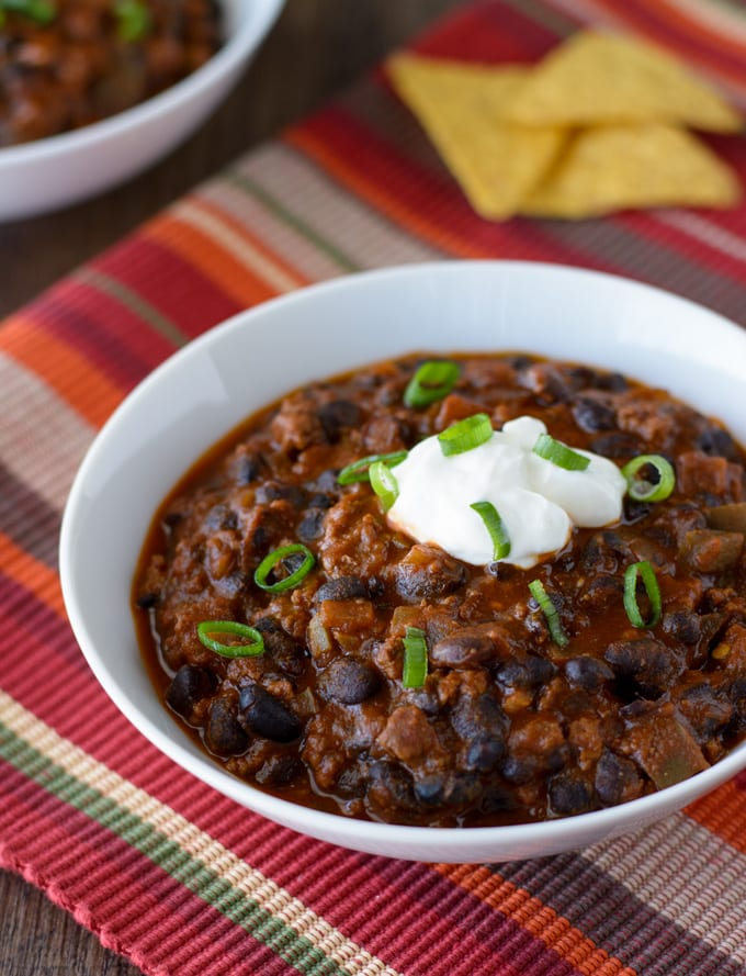 Two bowls of Chili con Carne with Beans and a few tortilla chips sitting on the side.
