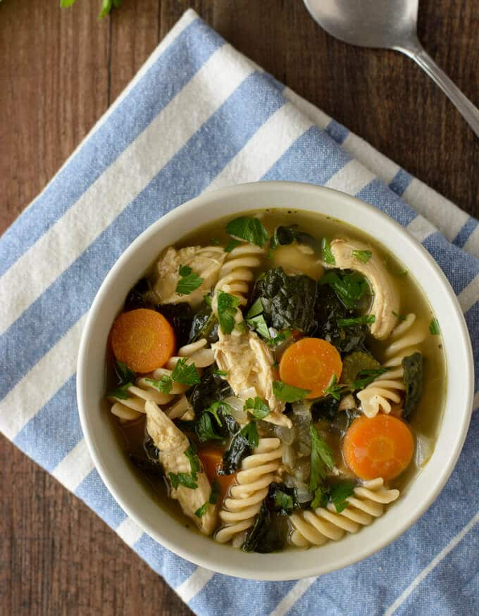 A bowl filled with shredded chicken, kale, noodles, sliced carrots and chicken broth.
