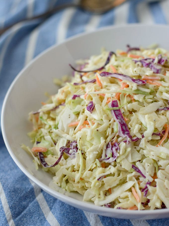 A large bowl of healthy coleslaw sitting on a towel.