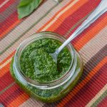 A small mason jar filled with spinach-basil pesto.