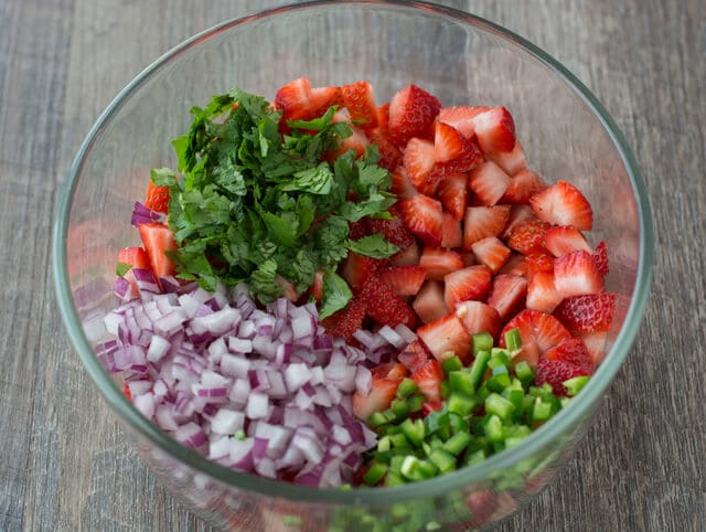 A glass bowl with diced strawberries, jalapenos, cilantro and red onion.