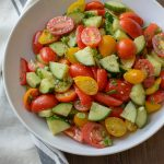 A large bowl with Tomato and Cucumber Salad tossed with a Parmesan Garlic Vinaigrette.