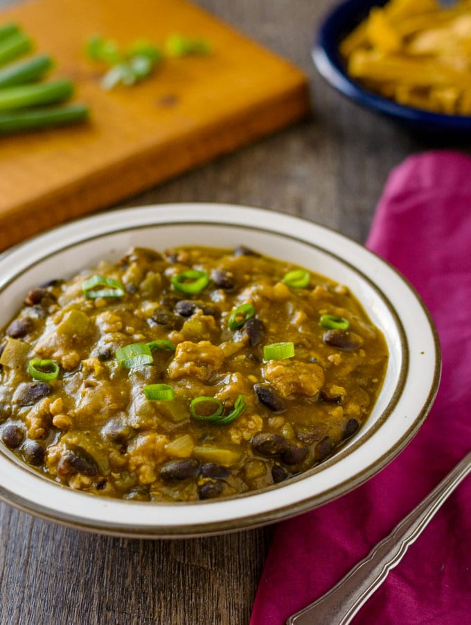 A cream colored bowl containing turkey pumpkin chili made with ground turkey and black beans.