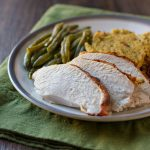 Sliced turkey breast on a plate with cornbread dressing and green beans.